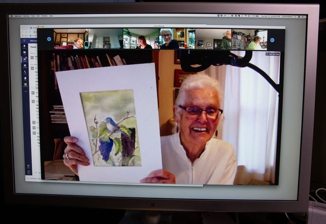 Ninety-two-year-old artist Carol Fourtner holds up a watercolor she painted to her class during one of their weekly Zoom classes held through the River Road Parks and Recreation District in Eugene.