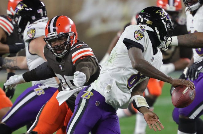 Ravens quarterback Lamar Jackson narrowly escapes Browns defensive end Myles Garrett as he scrambles for yards during the first half Monday, Dec. 14, 2020, in Cleveland, Ohio. [Jeff Lange/Beacon Journal]