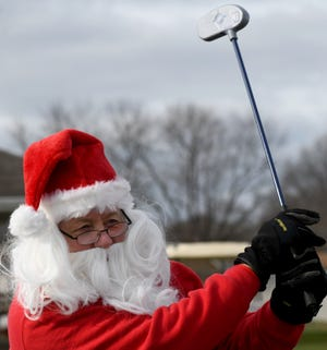 Santa (aka Program Director Terry Taylor) takes a practice swing Tuesday during The First Tee of Canton Holiday Drive Thru.