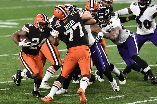 Browns running back Nick Chubb (24) breaks through the line behind the block of offensive guard Wyatt Teller (77) during the second quarter against the Baltimore Ravens, Dec. 14, 2020, at Cleveland. [Ken Blaze/USA TODAY Sports]