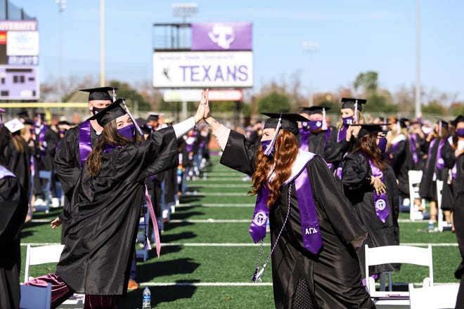 Tarleton State University graduates give each other a high-five during commencement ceremonies held last weekend at Memorial Field.