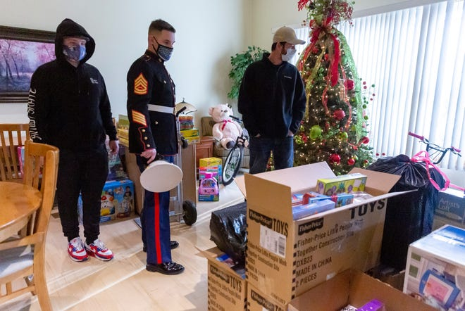 """Retired Gunnery Sgt. Justin Driscoll, center, with the U.S. Marine Corps Reserves Toys for Tots Program, along with his son, Jayden Driscoll, left, looks over the piles of toys gathered by residents at the Seasons Under the Oaks senior independent living center with CEO Zane Zaubi, right, as they prepare to load them onto a box truck on Tuesday in Springfield. For the past 15 years, residents, staff and the Zaubi family, the owners and operators of both Seasons Pine Creek and Seasons Under the Oaks, have worked together to organize a toy drive for Christmas. This year with the COVID-19 pandemic, the staff worked with residents to help shop online to gather enough toys to fill a box truck for the Toys for Tots program. """"I'm just astonished, honestly,"""" said Driscoll of the amount of toys that was donated. """"The pandemic has affected people in so many different ways. To see that here, they haven't let that sway them from their donations to helping the kids."""" [Justin L. Fowler/The State Journal-Register]"""