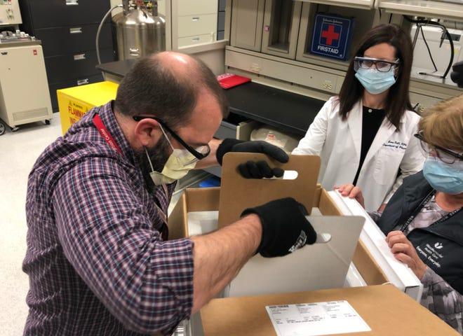 UMass Memorial clinical pharmacists Chris Manzi, left, and Lorie Gull, receive a vaccine shipment.