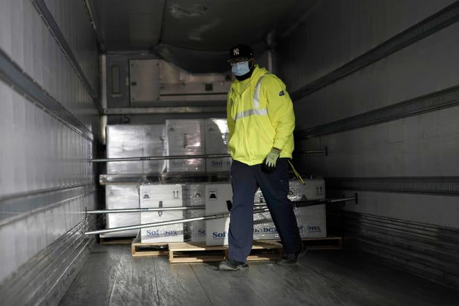 A worker places boxes containing the Pfizer-BioNTech COVID-19 vaccine on a truck to be shipped at the Pfizer Global Supply Kalamazoo manufacturing plant in Portage, Mich., Sunday.