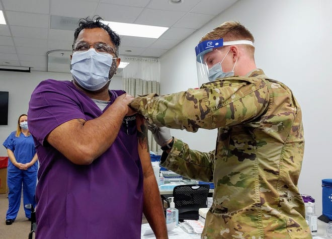 Roni Paul, an emergency room nurse and nurse educator, receives the COVID-09 vaccine from Spc. Adam G. Millett.