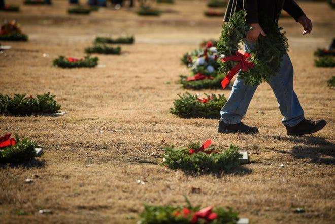 Volunteers place wreaths on graves in 2017 at Sandhills State Veterans Cemetery.