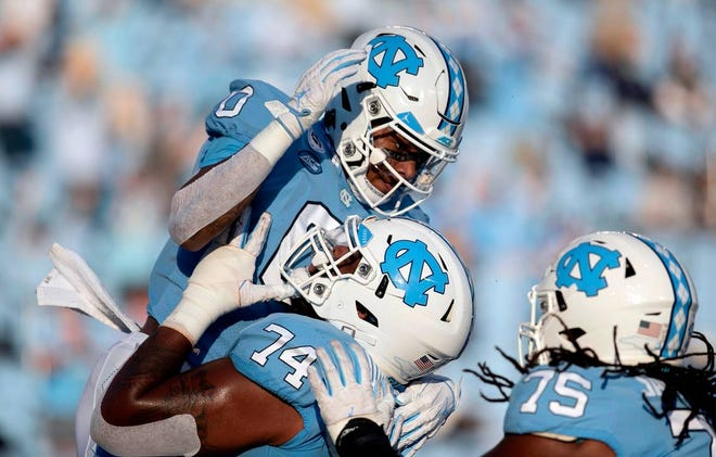 North Carolina receiver Emery Simmons, top, celebrates with offensive linemen Jordan Tucker and Joshua Ezeudu, right, after catching a touchdown pass against Notre Dame.