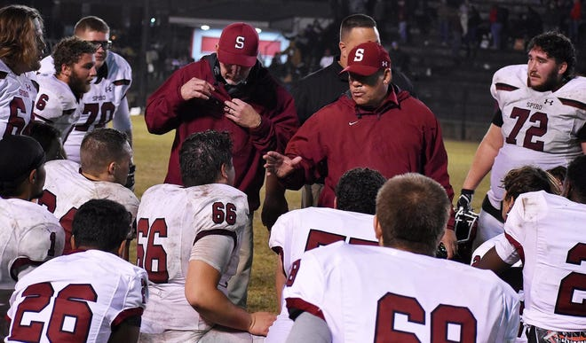 Spiro football coach Chris Bunch, center, addresses his team during a game this past season. Bunch announced Tuesday he is retiring after 31 seasons as the Bulldogs' coach, winning 228 games.