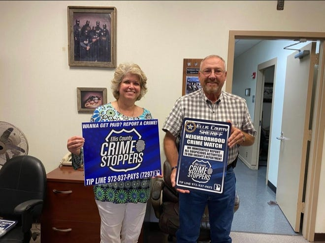 Ellis County Sheriff's Office Chief Deputy Mitch Bartley (right) displays Ellis County Crime Stoppers signs alongside Shari Phillips (CSEC Exec. Chair). Signs are also being provided for the inside of the Ellis County Jail.