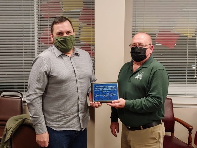 Former village trustee Jeremy Cole, left, accepts a plaque from Deputy Mayor Jeff Monroe thanking him for his service to the village.