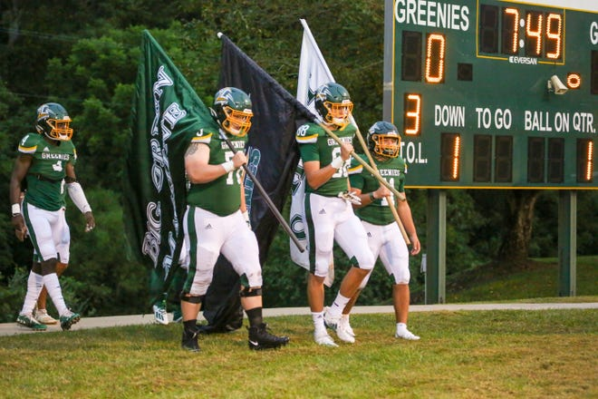 Christ School's Ian Adams, left, Charlie Browder, center, and Cade Mintz bring the flags out onto the field before a game earlier this season.