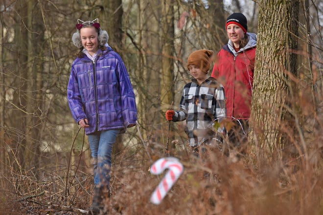 Keri Pope, of Bloomville, and her children Lexi, 11, and Kellen, 9, explore Lowe-Volk Nature Center on Tuesday morning as they search for candy canes during the Candy Cane Hike.