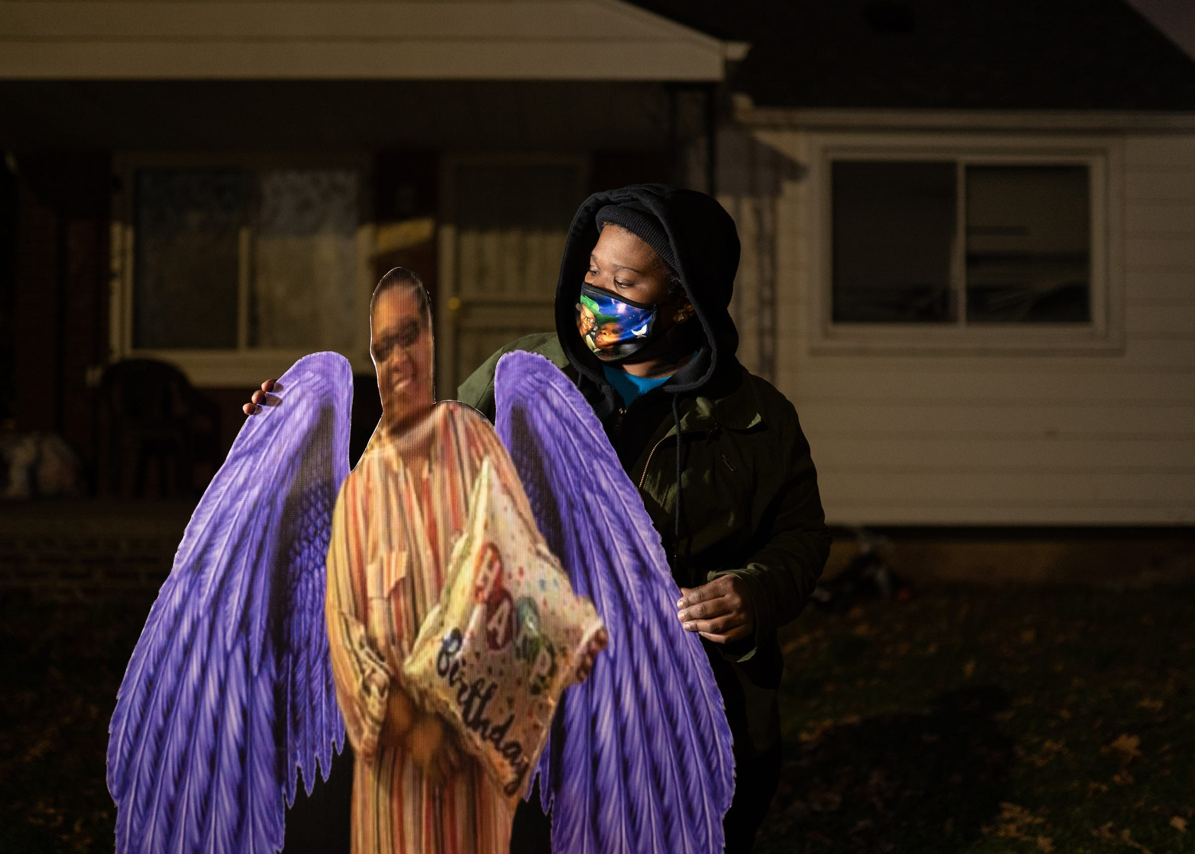 Juliette Gilbert, 33, of Detroit stands with a cutout of her mother, the late Monique Baldridge, 52, who died due to COVID-19 outside of her home in Detroit on Friday, December 11, 2020. Her mother fell ill in March 2020 and was hospitalized for about two weeks. Gilbert said her mother lived with her and her three kids.