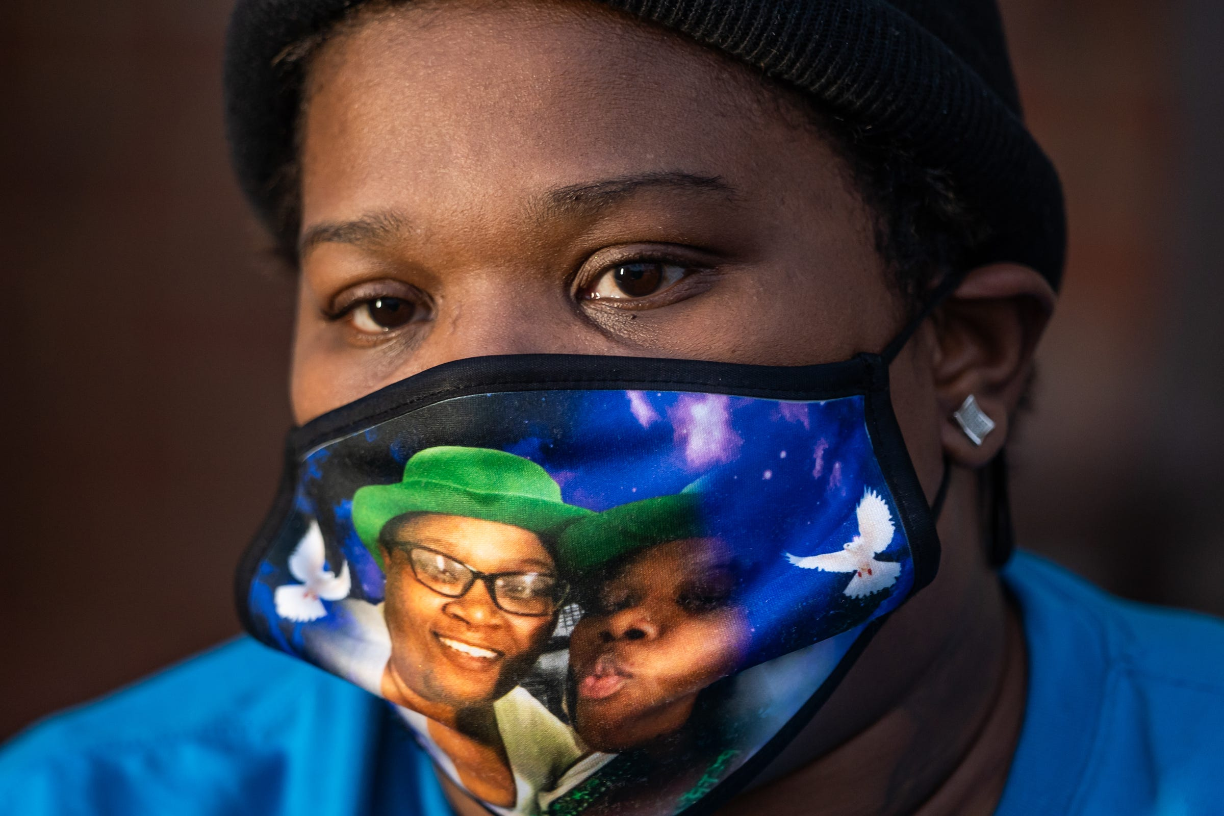 Juliette Gilbert, 33, of Detroit, speaks about losing her mother Monique Baldridge, 52, to COVID-19 while sitting outside of her home on Detroit's east side on Friday, Dec. 11, 2020, as she wears a mask of her and her mother from a St. Patrick's Day outing last year. Baldridge died on March 27, 2020.