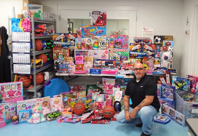 Mike Rodriquez shows off the collection donated at Revere Plastics for Toys for Tots.