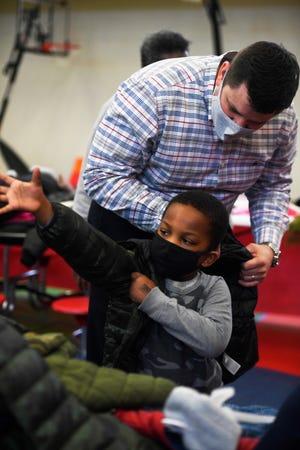 School Board member AJ Massey helps the children try on a new coat at Head Start Washington Douglas in East Jackson, Tenn., Tuesday, Dec. 15, 2020.