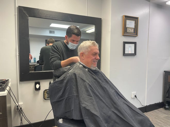 Lucky Clipper Barber Shop owner Conner Street trims Thomas Parent's hair at his new barbershop in Fowlerville, Tuesday, Dec. 15, 2020.