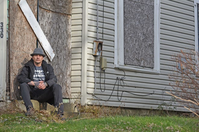 Jason Knasinski sits outside a boarded house at 330 Newman Street in Mansfield, which he is renovating into a new transitional shelter. Knasinski started a nonprofit called Stronger By Choice to help men who have been in shelter move forward with their lives.