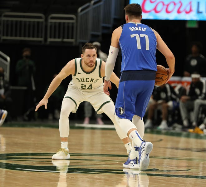 The Bucks' Pat Connaughton guards the Mavericks' Luka Doncic on Monday night.