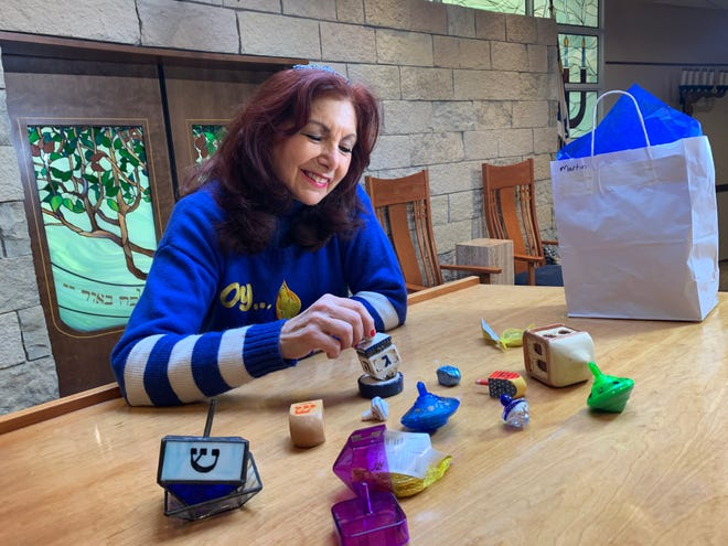 Deborah Martin, Congregation Emanu-El of Waukesha's cantor and spiritual leader, plays with a porcelain dreidel, one of many in her collection, inside the sanctuary of the Waukesha temple during Hanukkah. A dreidel was included in each gift bag picked up by congregation members before the start of Hanukkah this year, helping family's celebrate at home during the coronavirus pandemic.