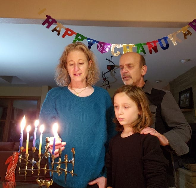 Jill and Mike Weinshel light their Hanukkah menorah on Dec. 14 at their Mequon home with their son, Eli.