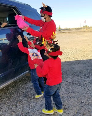 Luis Armendariz, 10, hands out a Christmas stocking filled with a small toy and goodies on Sunday while Emmanuel, 3, and Juandiego, 2, assist in Columbus, NM.