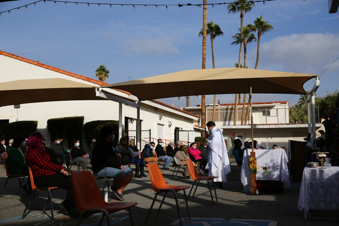Father David Foxen presides over an outdoor mass at Our Lady of Solitude Church in Palm Springs, Calif., on Saturday, December 12, 2020.