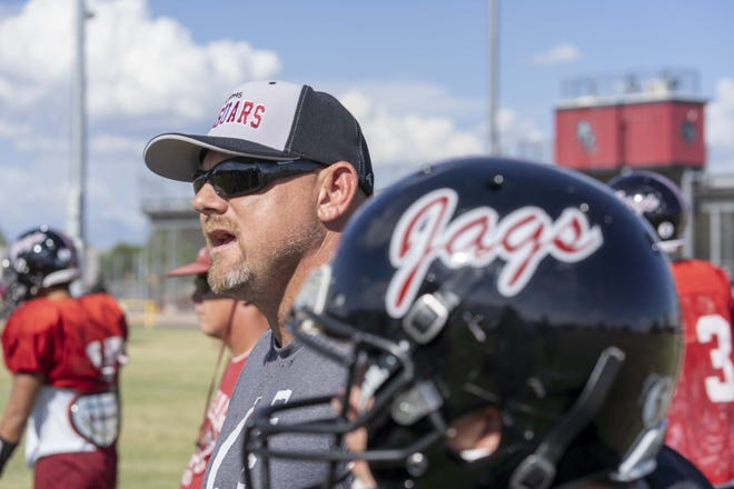Desert Ridge High School football head coach Jeremy Hathcock coaches his players during their football practice in Mesa, Az.