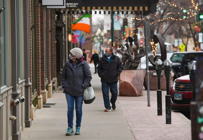 People wear masks in accordance with the city mandate while shopping downtown on Tuesday, December 15 in Sioux Falls.