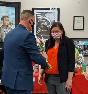 Wichita Falls ISD Superintendent Mike Kuhrt, left, presents a bouquet to Kirby Middle School Principal Shannon Cunningham in recognition of her being named Principal of the Year by the Texas Association of Secondary School Principals.