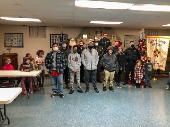 A group of children went inside the FOP Lodge Monday evening to share a meal with officers before taking their Christmas gifts home with them.