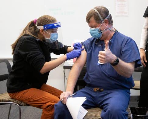 Nursing student Abriana Martinez administers the Pfizer coronavirus vaccine to Dr. Erik Pronske at the University of Texas Health Austin Dell Medical School on Tuesday December 15, 2020.