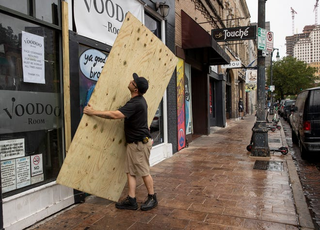 A worker puts boards over the windows of a bar on East Sixth Street on June 26, after Gov. Greg Abbott ordered bars in Texas to close due to the coronavirus pandemic. The Paycheck Protection Program, which was put together quickly early in the pandemic to provide forgivable loans to U.S. businesses with 500 or fewer employees, brought more than $3.5 billion into the Austin-area economy, according to government data.