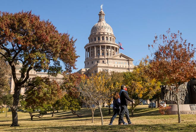 A couple take a stroll on the grounds of the Texas Capitol on Wednesday, December 16, 2020. [AMERICAN-STATESMAN/FILE]