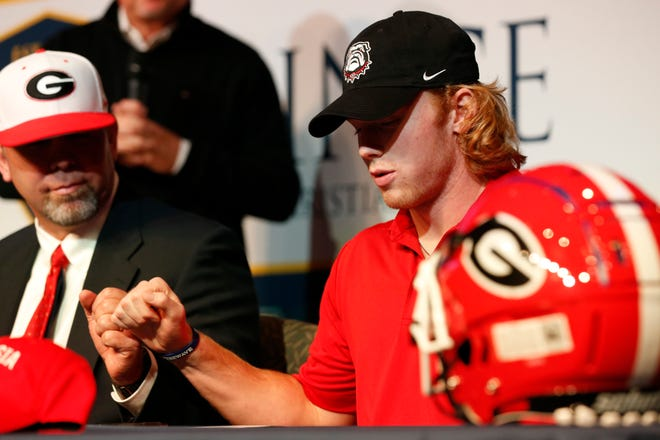 Prince Avenue Christian quarterback Brock Vandagriff fist bumps with his dad and football coach Greg Vandergriff after signing to play football for the University of Georgia at a Signing Day ceremony at his high school in Bogart, Ga., on Wednesday, Dec. 16 2020. (Photo/Joshua L. Jones, Athens Banner-Herald)