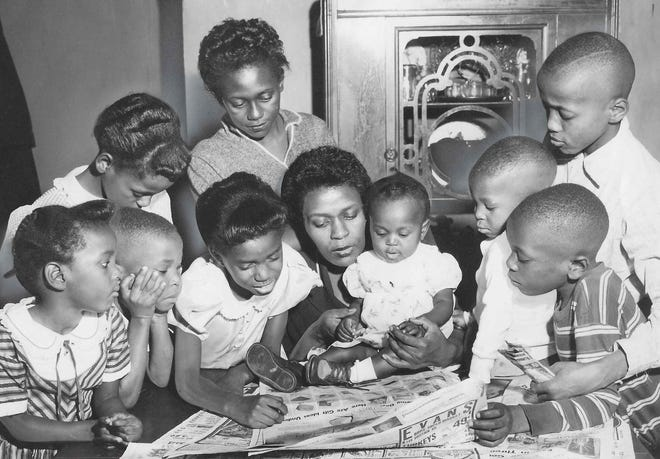 Helen Arnold sits at a table with her nine children Dec. 23, 1955, to look for gift ideas in the Beacon Journal after receiving $100 from a mysterious benefactor in Akron. The kids, from left, are Carla, 3, Gary, 5, Mona, 9, Gale, 8, Cathy, 14, Donna, 7 months, Gerald, 2, John, 7, and Royal, 11.