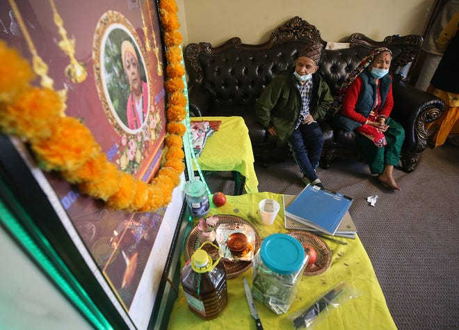 Loved ones gather to mourn the death of Phul Acharya during a Hindu funeral ceremony at the family's home Dec. 4 in Cuyahoga Falls. She died Nov. 25 from COVID-19.