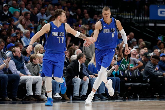 Dallas Mavericks' Luka Doncic (77) and Kristaps Porzingis (6) celebrate a basket by Porzingis on Oct. 27, 2019, in the second half against the Portland Trail Blazers in Dallas. The NBA restart means Doncic and  Porzingis are all but assured of making their playoff debuts in their first season on the court together with Dallas.