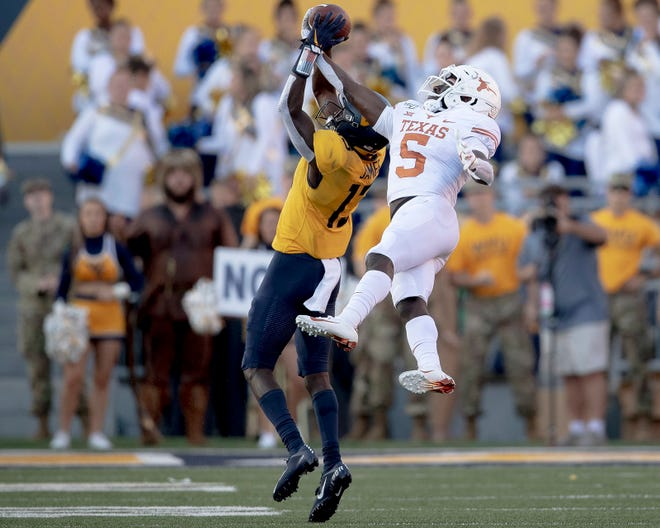 Texas defensive back D'Shawn Jamison (5) intercepts a pass intended for West Virginia receiver Sam James (13) on Oct. 5, 2019 in Morgantown, W. Va.