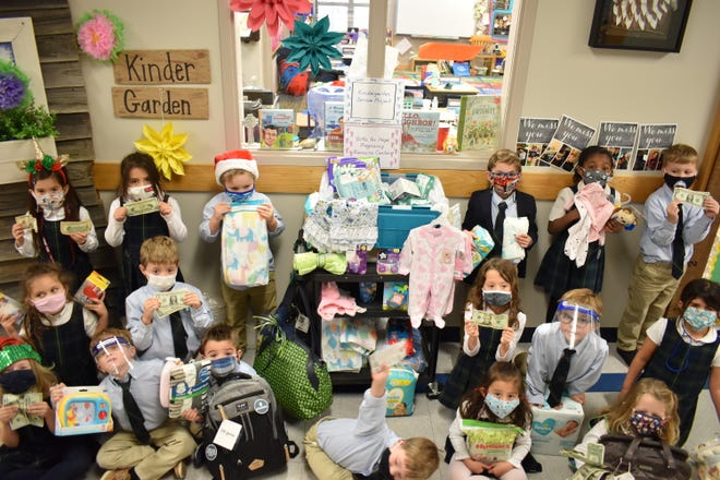 The Oak Hall Episcopal School class of Jimmie Wallis stands Wednesday with the items collected for the Hope Pregnancy Center. Rather than accept donated items, Wallis made students earn donations through service projects.