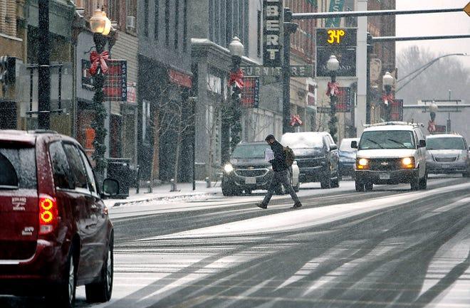 A pedestrian crosses West Main Street at Orange Street in downtown Ashland as the snow falls on Wednesday, Dec. 16, 2020. TOM E. PUSKAR/TIMES-GAZETTE.COM