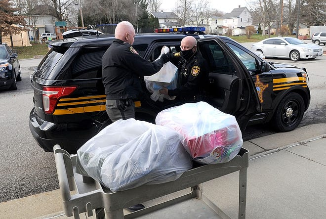 Ashland County Sheriff Capt. Dave Blake and Sgt. Don Sims unload the presents they purchased for the Salvation Army's Angel Tree on Tuesday. The sheriff and staff at the Ashland County Sheriff's Office were looking for a way to give back to the community this Christmas. They raised approximately $3,500 to purchase gifts for 35 children.