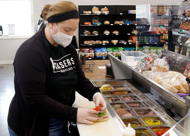Kayla Gasser adds the toppings to the Italian Stack sandwich at Gassers Marketplace in Creston. Gasser spotted a need in her hometown and set to work to fulfill it. TOM E. PUSKAR/TIMES-GAZETTE.COM