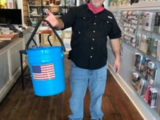 John Solomon holds up one of the blue buckets that's going to help raise money for the ECCC at next month's Butts & Clucks.