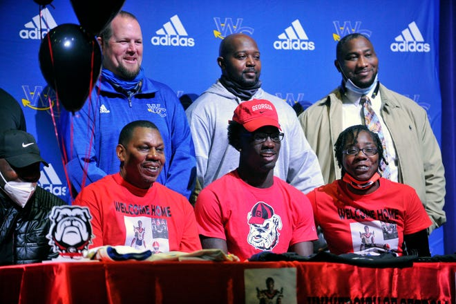 Lovasea Carroll, middle, poses with his parents and former Warren County coaches during his signing ceremony on Wedesday, Dec. 16, 2020 at Warren County High School. [WYNSTON WILCOX/THE AUGUSTA CHRONICLE]
