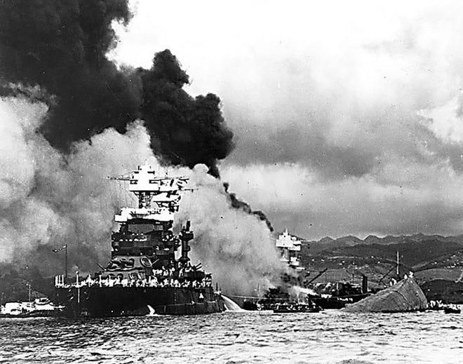 The capsized USS Oklahoma lies next to a slightly damaged USS Maryland.