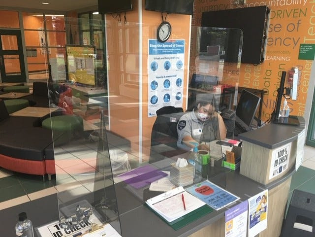 A divider and signs outlining COVID-19 safety precautions are set up at a Jasper County School District front desk.