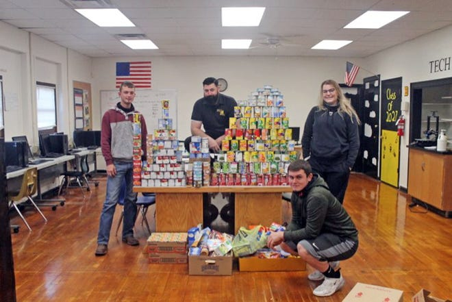 Jason Burnett, Chris Herriman, Hunter Shuffield, and Maddie Brandes stand with the food that was donated for Bunceton's holiday buddy packs.