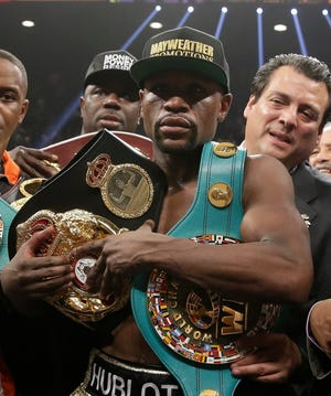 Floyd Mayweather carries the winner's belts after he defeated Manny Pacquiao in their 2015 welterweight title fight in Las Vegas.