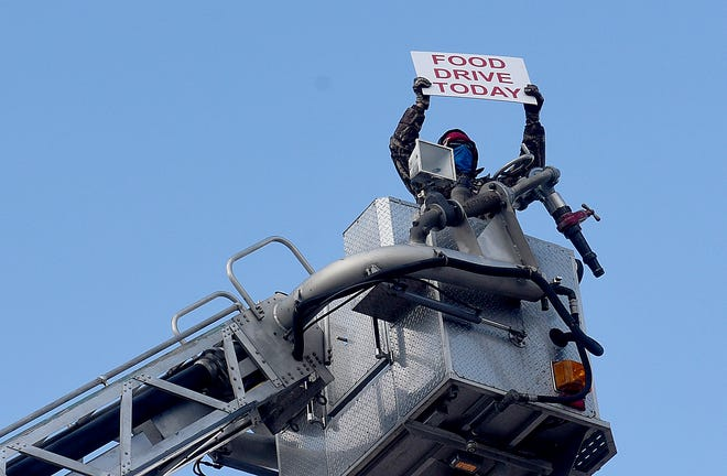 Y105 radio personality Cosmo holds a sign Wednesday from the top of a Columbia Fire Department ladder truck to advertise the One for One Holiday Food Drive.